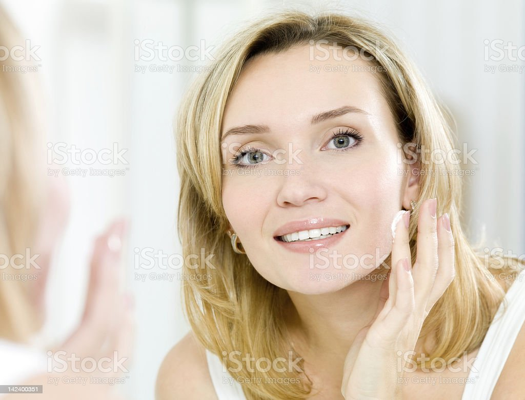 Beautiful woman applying cosmetic cream on face in mirror royalty-free stock photo