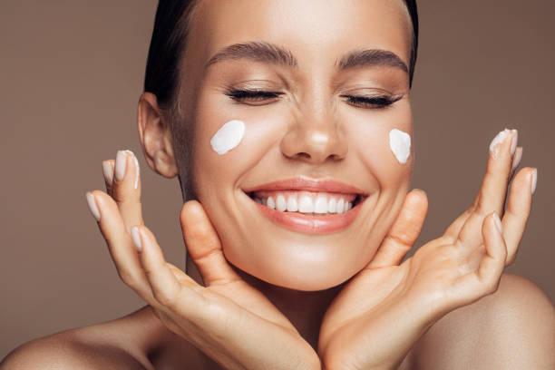 Beautiful woman applying cream on her face stock photo