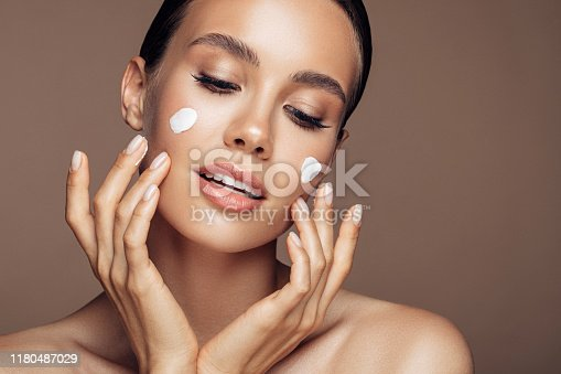 Beautiful woman applying cream on her face