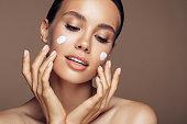 Beautiful woman applying cream on her face