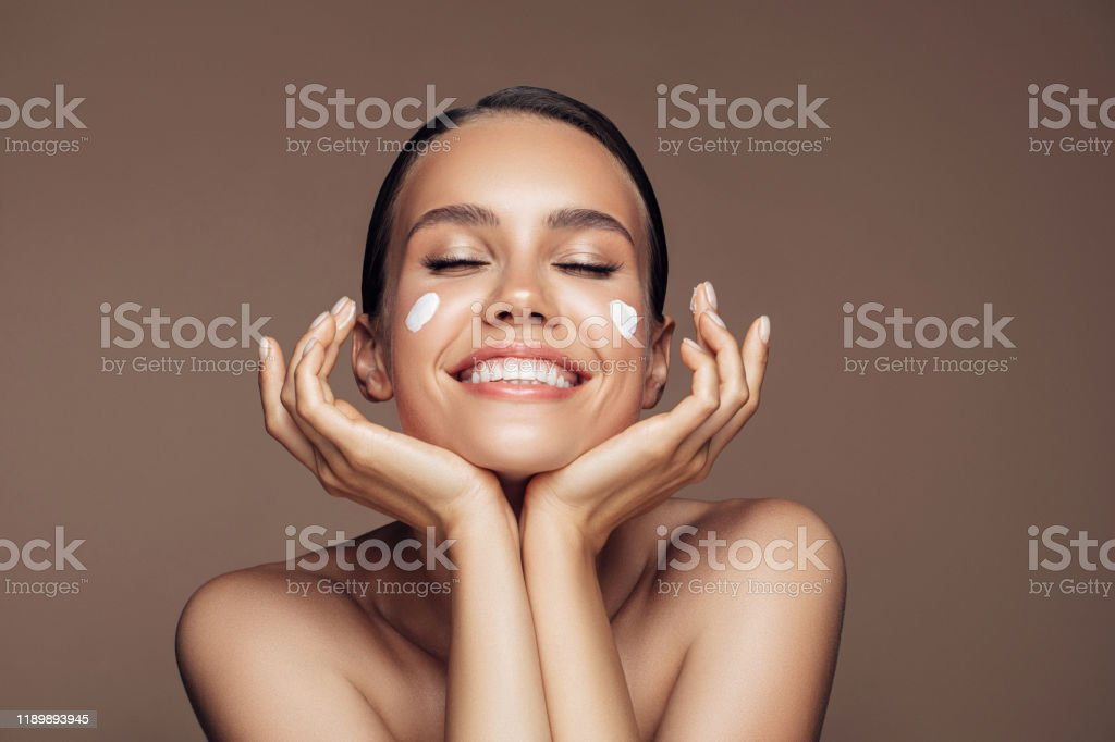 Beautiful woman applying cream on her face - Foto stock royalty-free di Accudire