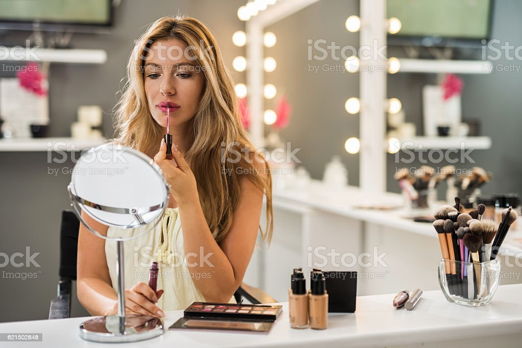 Beautiful woman applying lip balm while looking herself in mirror. foto stock royalty-free