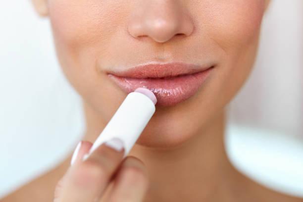 schöne frau lip protector auf lippen haut anwenden. schönheit - labello stock-fotos und bilder