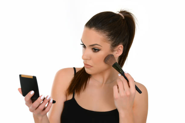 Beautiful woman applying make-up, holding make up brush and small mirror. – zdjęcie