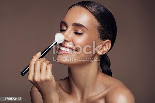 istock Beautiful woman applying make-up 1176520415