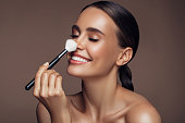 istock Beautiful woman applying make-up 1176520415