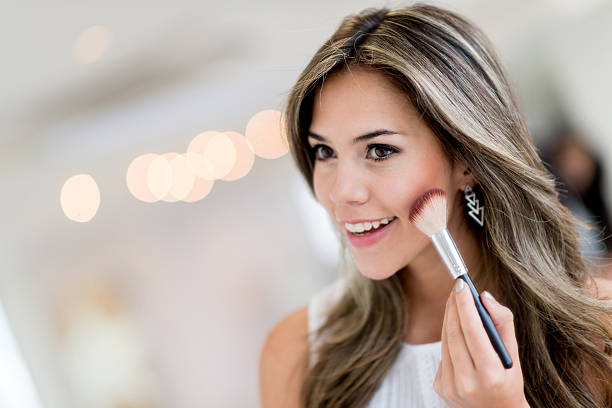 Beautiful woman applying makeup Beautiful woman applying makeup with a brush and smiling blusher make up stock pictures, royalty-free photos & images