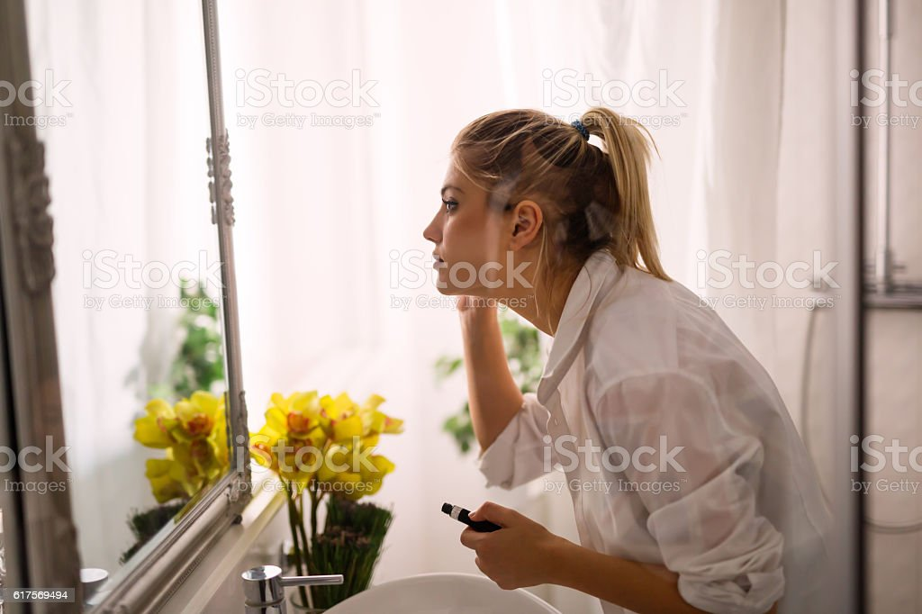 Beautiful woman applying makeup Beautiful woman applying makeup at home Adult Stock Photo