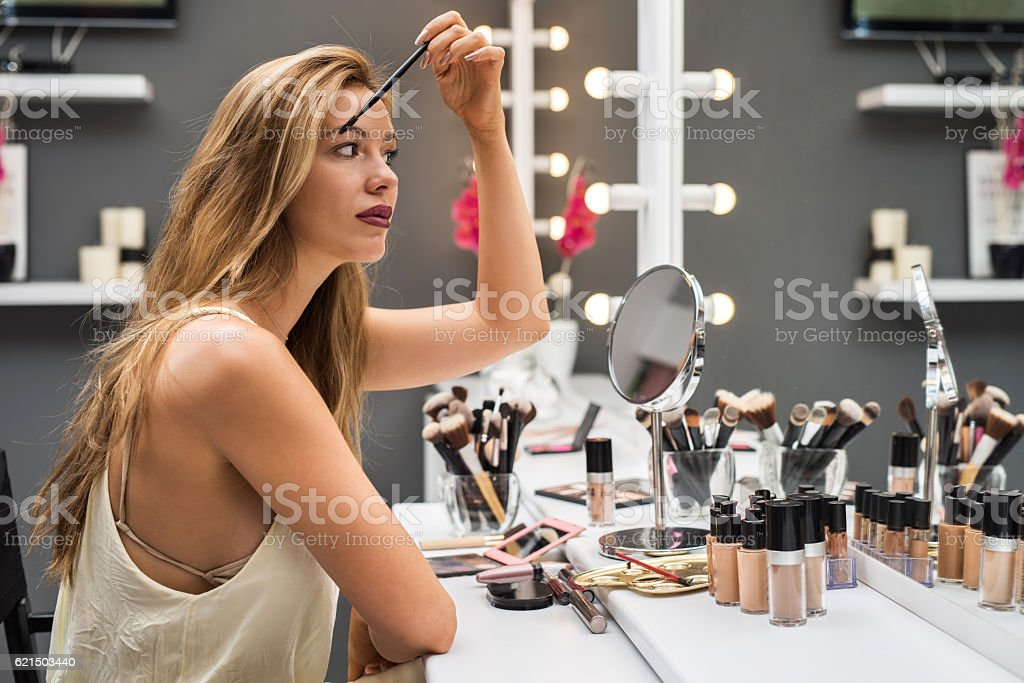 Beautiful woman applying mascara in front of a mirror. foto stock royalty-free