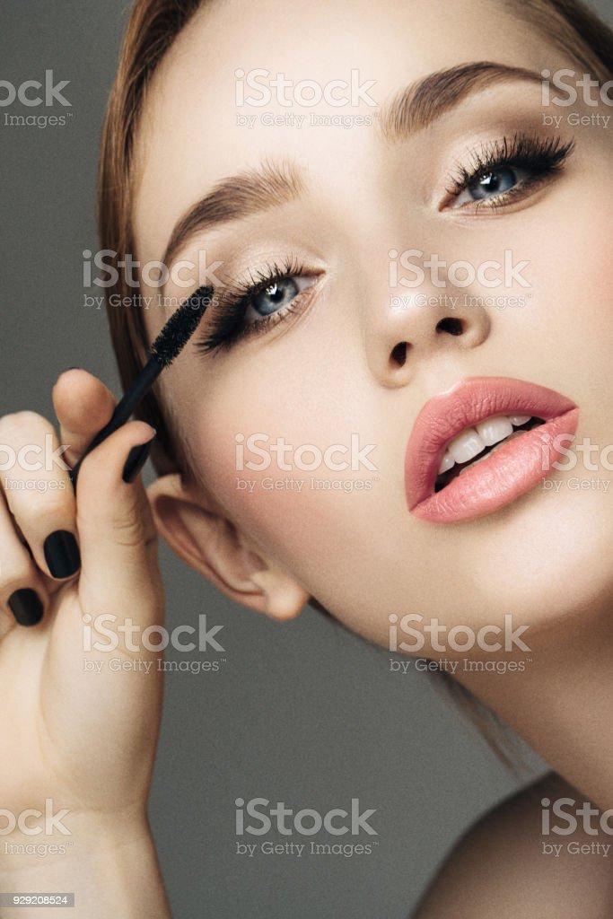 Beautiful woman applying mascara stock photo
