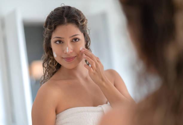 Schöne Frau, die Feuchtigkeitscreme auf ihr Gesicht auftragen – Foto