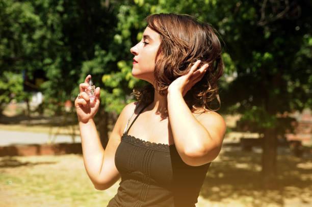 Linda mulher aplicar perfume no parque - foto de acervo