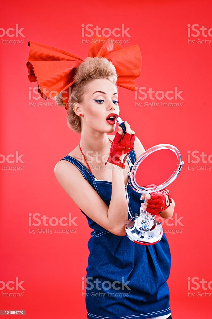 Beautiful woman applying red lipstick stock photo