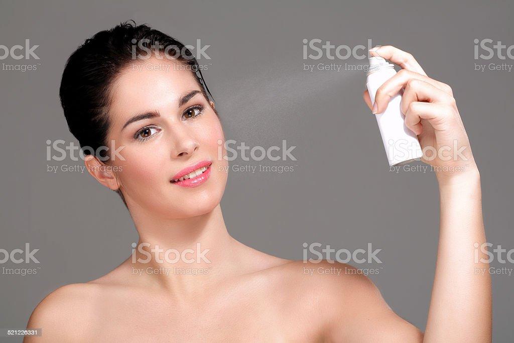 Beautiful woman applying spray water on face stock photo