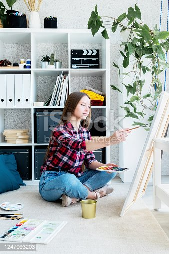 937313030 istock photo Beautiful woman artist painting a picture at home 1247093203