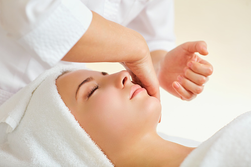 istock Beautiful woman at a facial massage at a spa salon 921797362