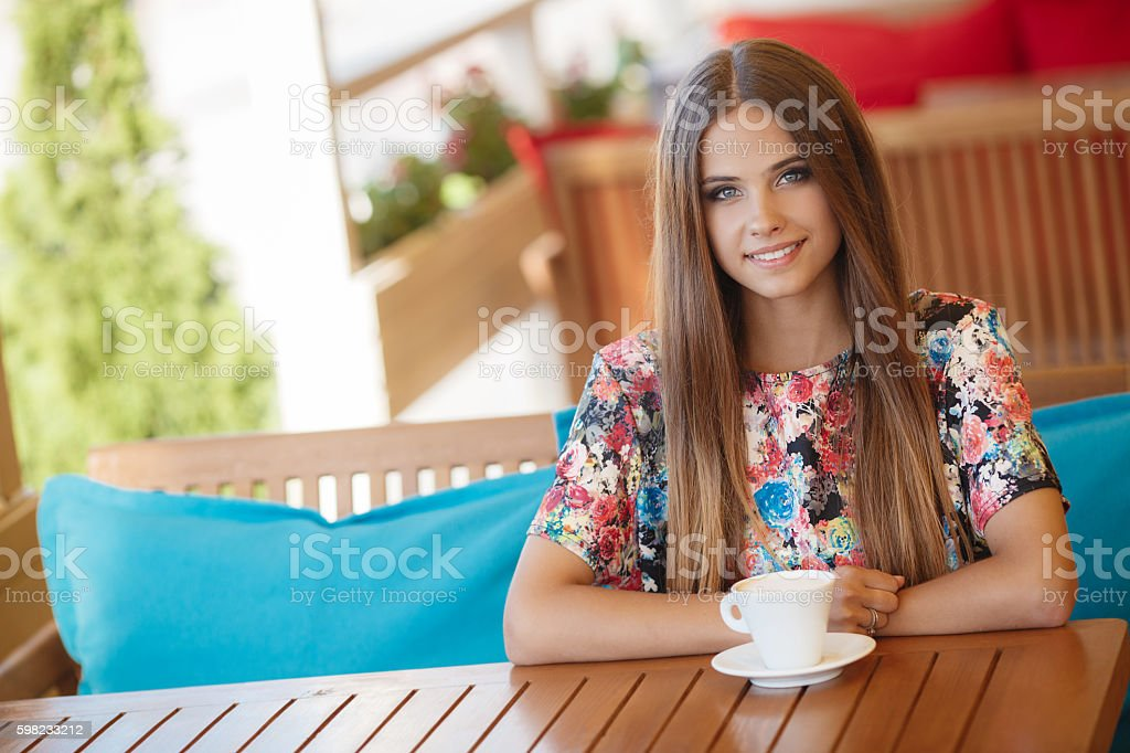 Beautiful woman at a table in summer cafe foto royalty-free