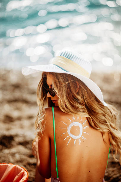 Beautiful woman at beach using sun lotion stock photo