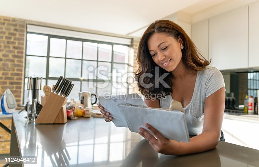 Portrait of a beautiful woman at home checking the mail and looking happy –lifestyle concepts