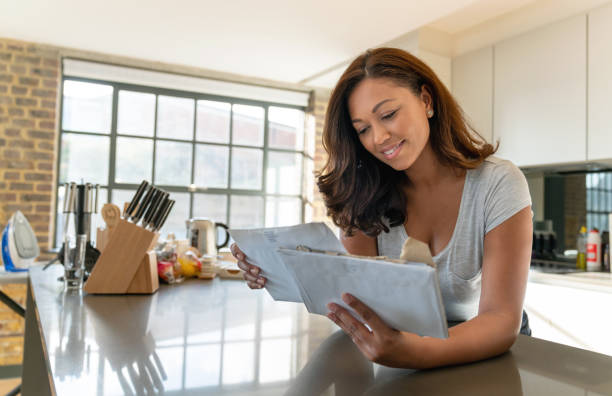Beautiful woman at home checking the mail Portrait of a beautiful woman at home checking the mail and looking happy –lifestyle concepts mailbox stock pictures, royalty-free photos & images