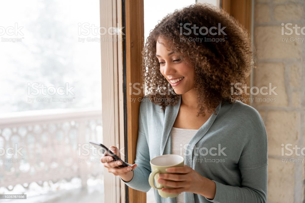 Schöne Frau zu Hause trinken eine Tasse Kaffee und SMS auf ihr Handy – Foto