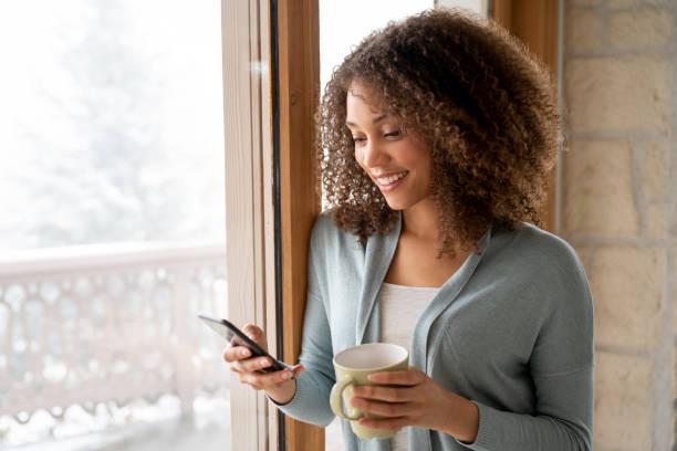 belle femme à la maison boire une tasse de café et envoyer des sms sur son téléphone - europe centrale photos et images de collection