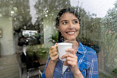 Beautiful woman at home looking through the window on a rainy day enjoyng a cup of coffee smiling