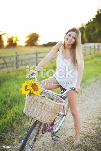Young beautiful woman with a bike at summertime.