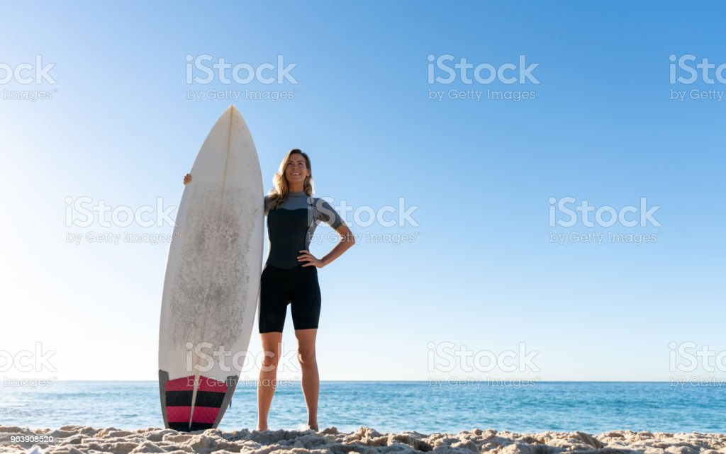Beautiful woman at the beach surfing and looking happy - Royalty-free Adult Stock Photo