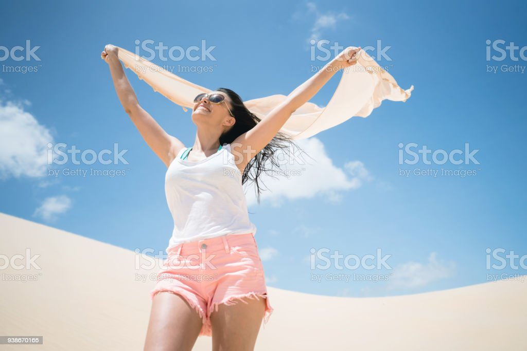 Portrait of a beautiful woman at the desert holding a sarong and...