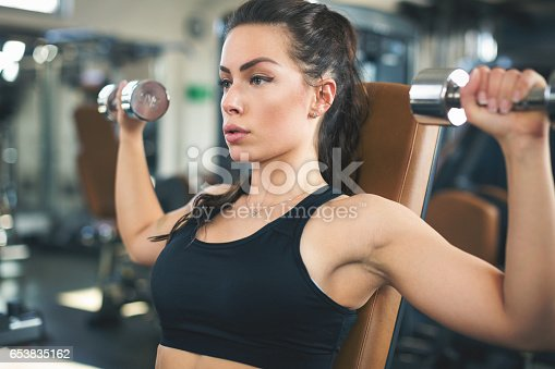 670937518istockphoto Beautiful woman at the gym exercising with dumbbells 653835162