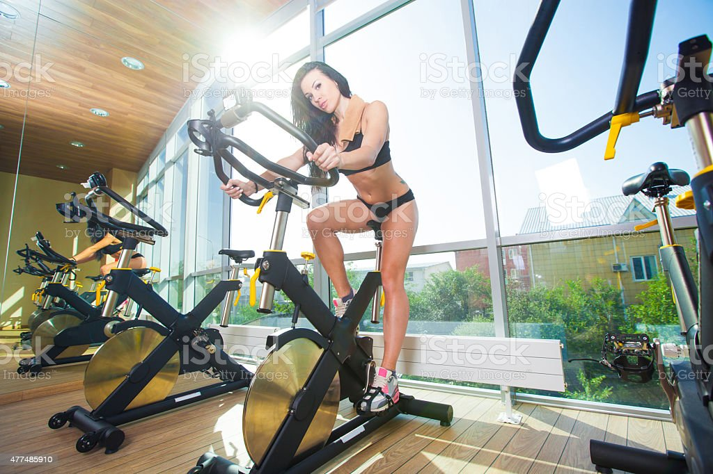 Beautiful woman at the gym on bike, cycle, sunny gym stock photo