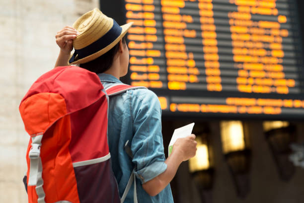 beautiful woman at the train station. - arrival departure board stock photos and pictures