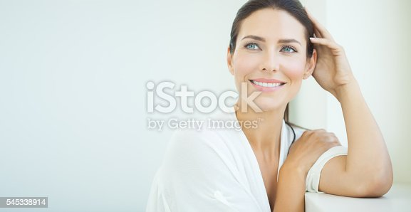Beautiful woman sitting at window. Light blue and white day light and high key.