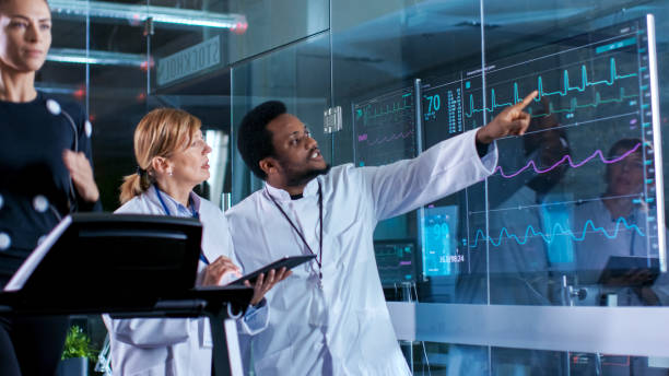 Beautiful Woman Athlete Runs on a Treadmill with Electrodes Attached to Her Body, while Two Scientists Supervise Watching EKG Data Showing on Laboratory Monitors. stock photo