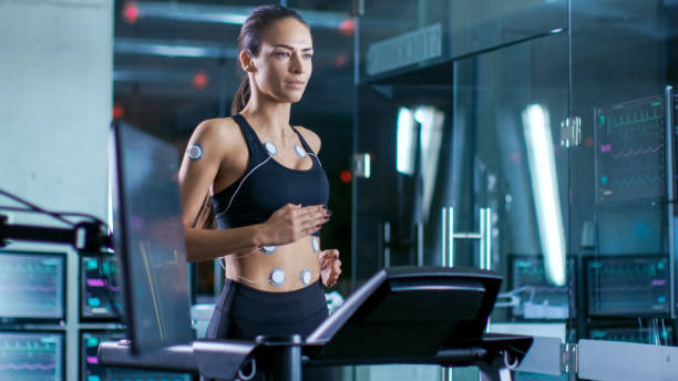 beautiful woman athlete runs on a treadmill with electrodes attached to her body, female physician uses tablet computer and controls ekg data showing on laboratory monitors. - carpet runner stock photos and pictures