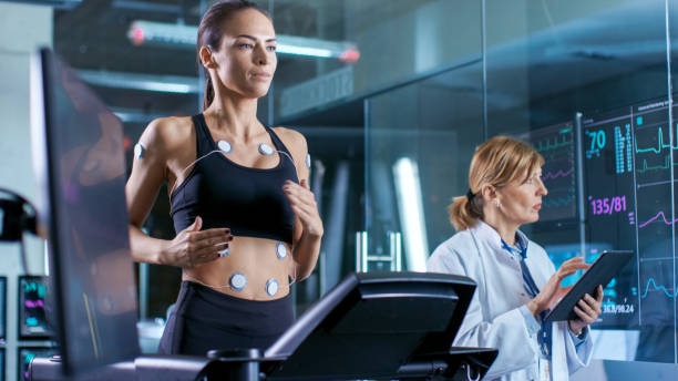Beautiful Woman Athlete Runs on a Treadmill with Electrodes Attached to Her Body, Female Physician Uses Tablet Computer and Controls EKG Data Showing on Laboratory Monitors. stock photo
