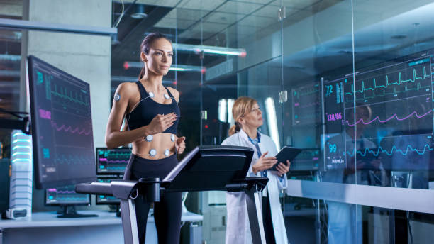 beautiful woman athlete runs on a treadmill with electrodes attached to her body, female physician uses tablet computer and controls ekg data showing on laboratory monitors. - sports medicine stock photos and pictures