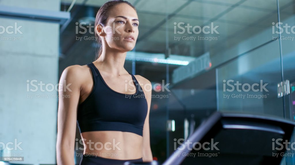 da7fcd02e8 Beautiful Woman Athlete Wearing Sport Bra Walks On A Treadmill Uses ...