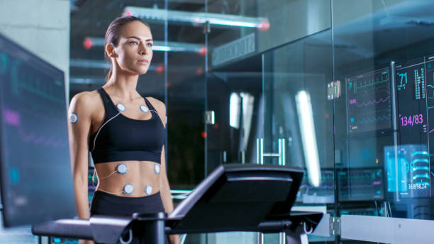 Beautiful Woman Athlete Wearing Sports Bra with Electrodes Connected to Her, Walks on a Treadmill in a Sports Science Laboratory. In the Background Laboratory. Medium Shot. stock photo