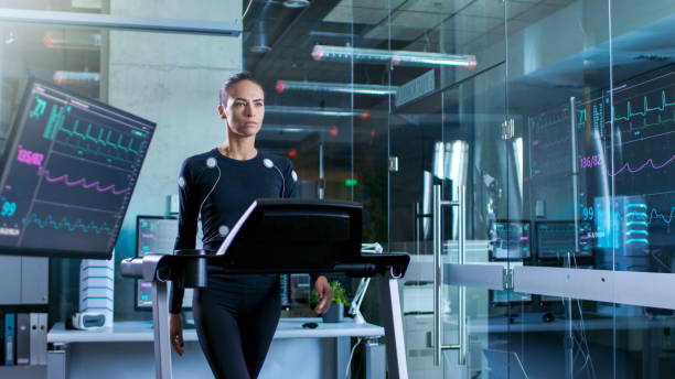 Beautiful Woman Athlete with Electrodes Connected to Her Body Walks on a Treadmill in a Sports Science Laboratory. In the Background High-Tech Laboratory with Monitors Showing EKG Readings. stock photo