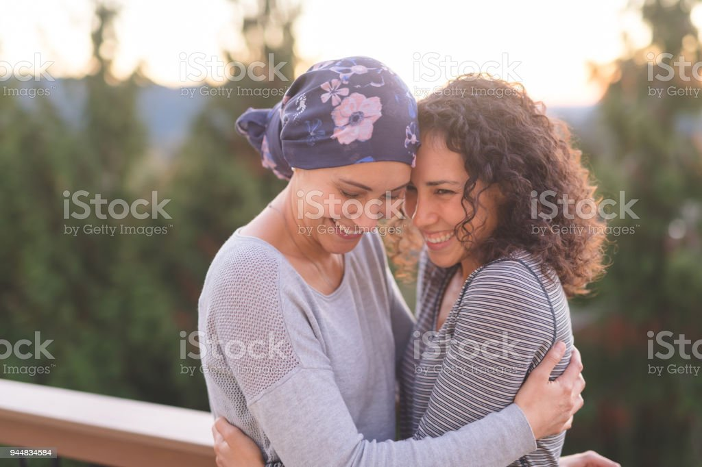 Beautiful ethnic woman battling cancer hugs her sister tightly stock photo