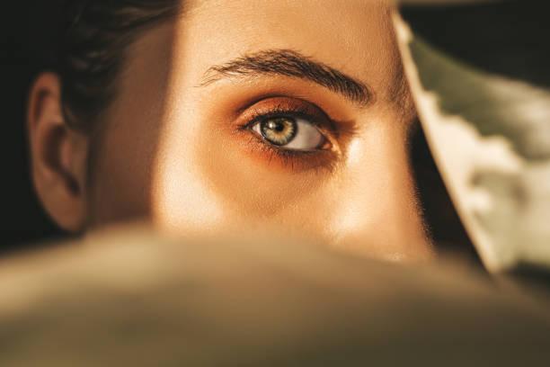 beautiful woman behind leaves - eye imagens e fotografias de stock