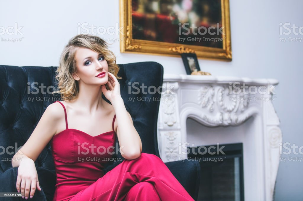 Beautiful woman blonde model in a red jumpsuit a fashionable and elegant interior stock photo