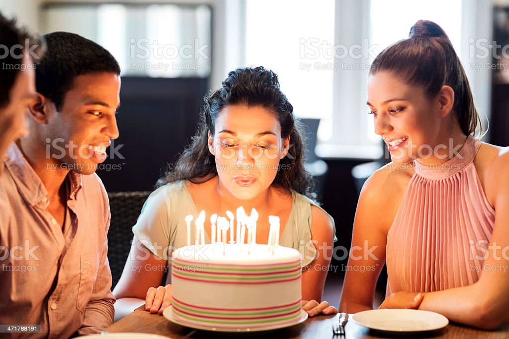 Beautiful Woman Blowing Birthday Candles On Cake stock photo