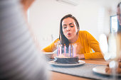 Beautiful young woman blowing candles on cake at dining table. Females are celebrating birthday party of friend. They are at home.