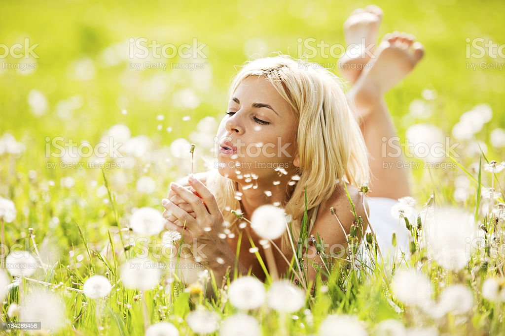 Beautiful woman blowing dandelions in the nature. royalty-free stock photo