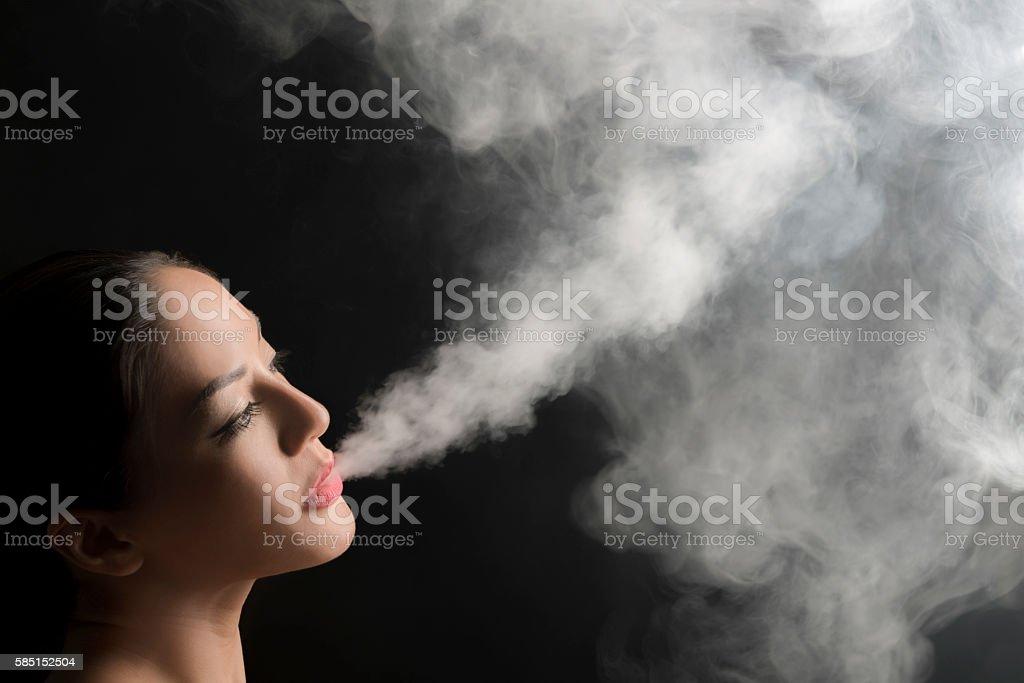 Beautiful woman blowing vape smoke. stock photo