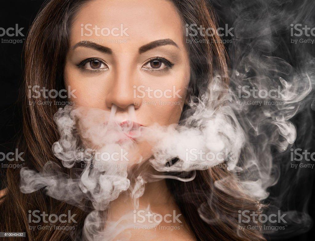 Beautiful woman blowing vape smoke stock photo