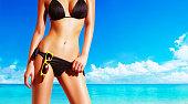 美しい女性のボディに黒のビキニで浜に立って。黄色のサングラス。完璧な肌を輝きます。